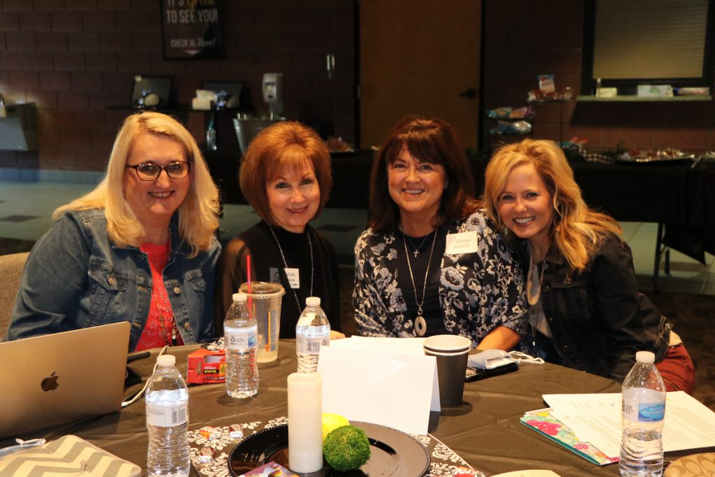 four women at a conference table networking