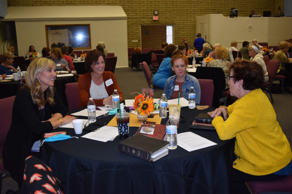 four women sitting at a table at a conference talking and networking