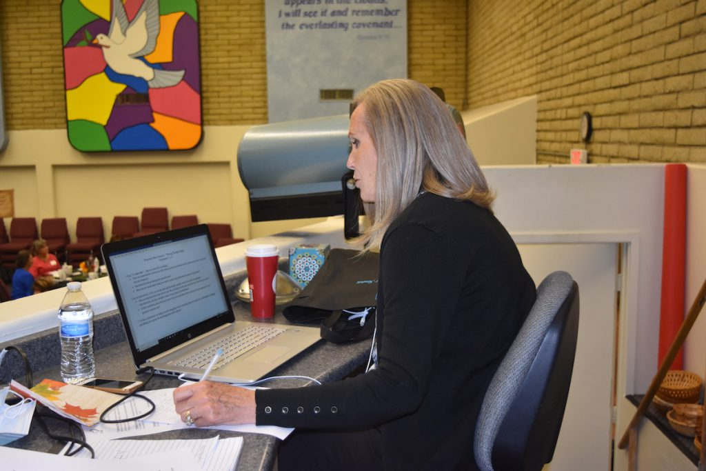 a woman in a black sweater working at a computer and writing
