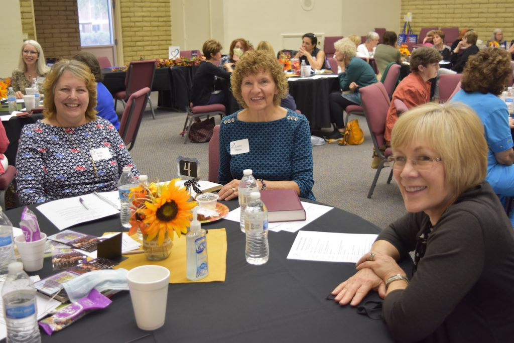 three women at a conference table sharing and networking
