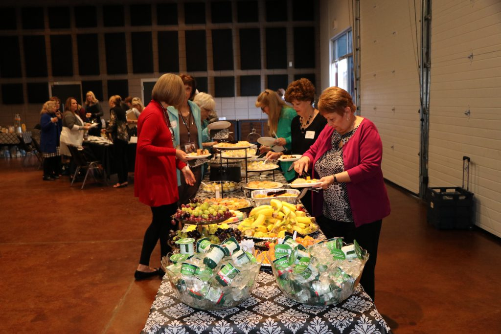 women at a conference in line to get food at a buffet line