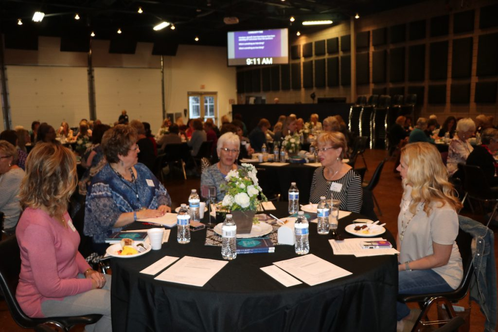 five women at a table at a conference talking and eating
